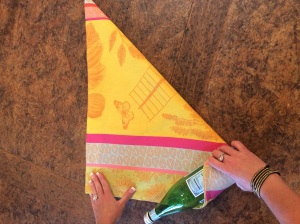 Align the bottom of the bottle along the long edge and begin wrapping the towel around the bottle.